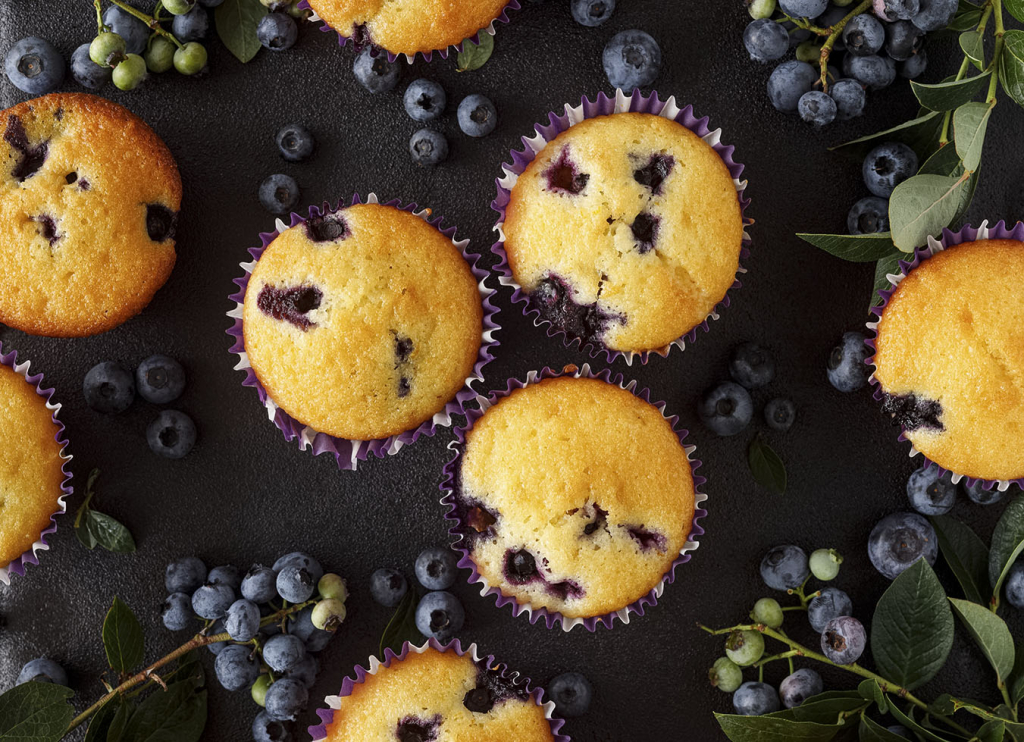 Blueberry muffins on a black background, top view
