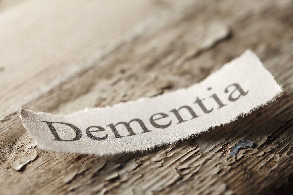 """The word 'Dementia"""" on a torn piece of paper that rests on an old weathered piece of wood.  The old paint is flaking off of the wood surface to help convey the feeling of age."""