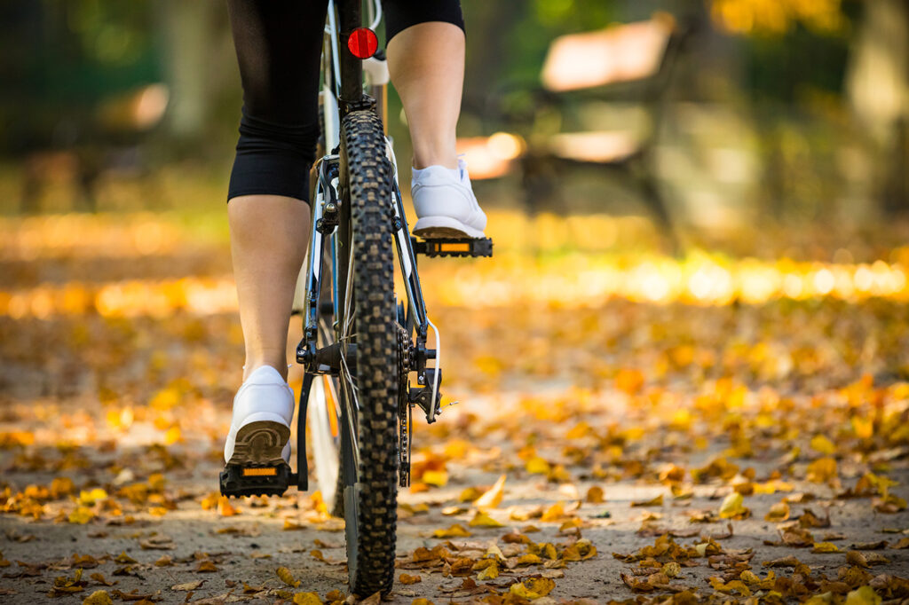 Urban biking - woman with bike in city park